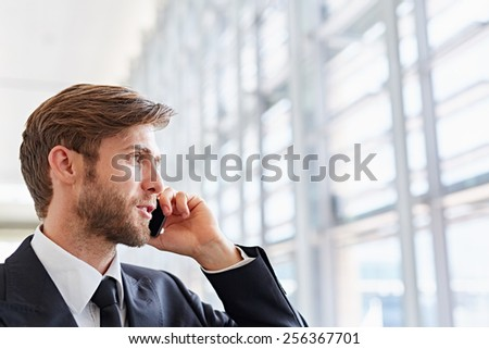 Closeup of a corporate executive looking away confidently while talking on his mobile phone - stock photo