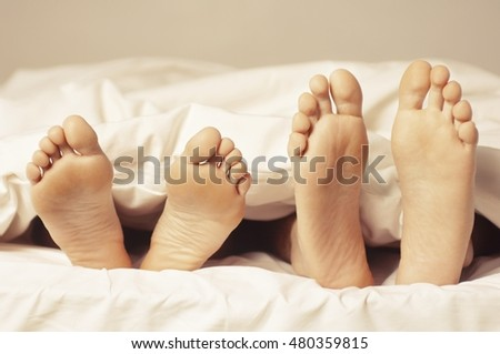 Closeup of a couple lying in bed barefeet