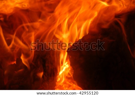Closeup of a cozy wood fire in the fireplace - stock photo