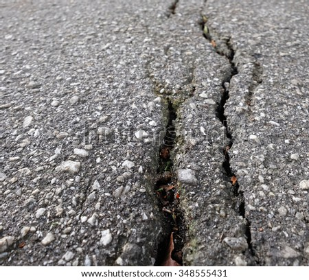 Closeup of a crack on the surface of a tarmac road.  - stock photo