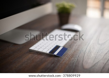 Closeup of a credit card sitting on a keyboard and ready for some online shopping. Photo with very shallow depth of field - stock photo