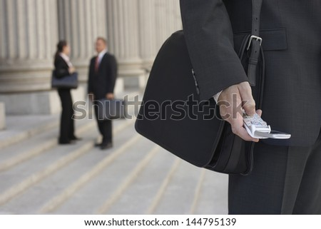 Closeup of a cropped businessman using cellphone and people talking in the background - stock photo