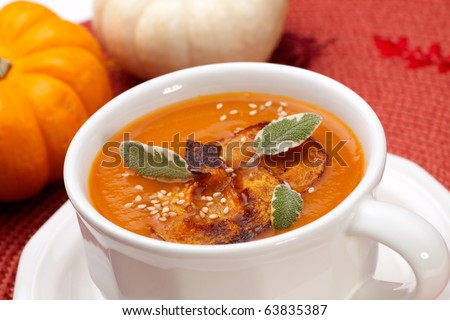 Closeup of a cup of hot delicious spicy roasted pumpkin soup with pumpkin crisps, sage and sesame seads.