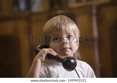 Closeup of a cute blond boy using telephone at home - stock photo