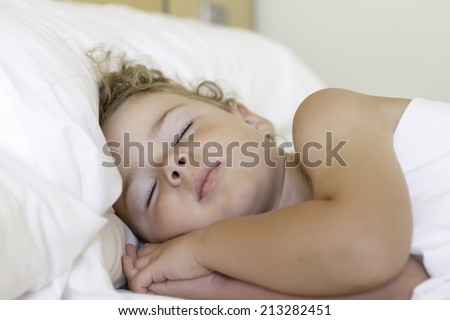 closeup of a cute little boy sleeping sideways in bed with entwined hands below the face - focus on the face - stock photo
