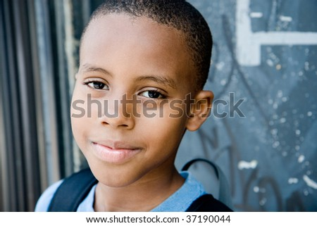 closeup of a cute smiling boy in an urban environment - stock photo
