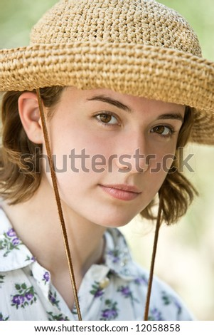 Closeup of a cute, thoughtful looking teenage girl in a straw hat and vintage flower print dress in the sunshine