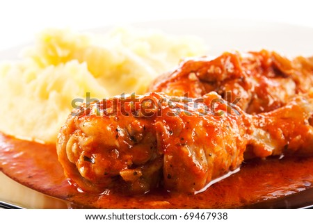 Closeup of a delicious dish with drumsticks in chili and tomato sauce with mashed potatoes
