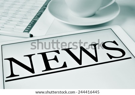 closeup of a desk with a cup of coffee and a tablet computer where to read the news - stock photo