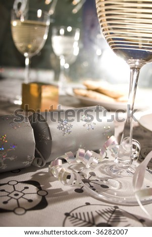 Closeup of a dining table set for Christmas with crackers, glasses of wine, mince pies, gift and streamer. - stock photo