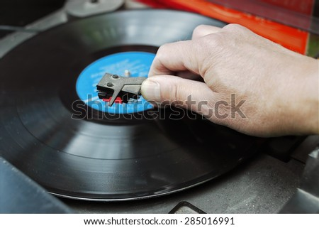 Closeup of a DJ hand on the turntable deck, outdoor shot with selective focus - stock photo
