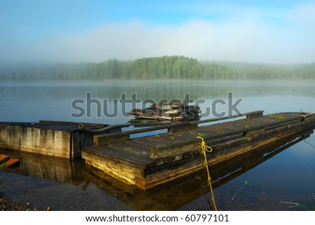 Closeup of a dock on a misty lake - stock photo