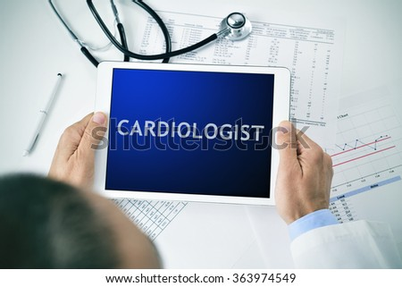 closeup of a doctor man sitting at his office desk holding a tablet computer with the word cardiologist in its screen - stock photo