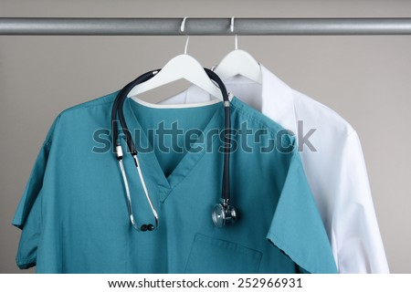 Closeup of a doctor's scrubs with stethoscope and lab coat on hangers against a neutral background. Green Scrubs and a white lab coat against a gray background.