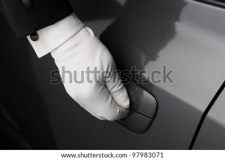 Closeup of a doormans hand on the latch of a car door. - stock photo