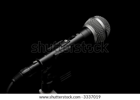 Closeup of a dynamic microphone isolated on black - stock photo