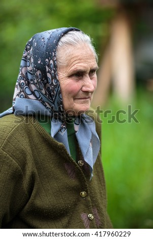 Closeup of a farmer woman in her seventies outdoor with selective focus - stock photo