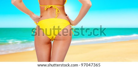 Closeup of a female backside in a yellow swimsuit. A day at a beach concept - stock photo
