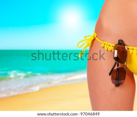 Closeup of a female body in a swimsuit with sunglasses. A day at a beach concept - stock photo