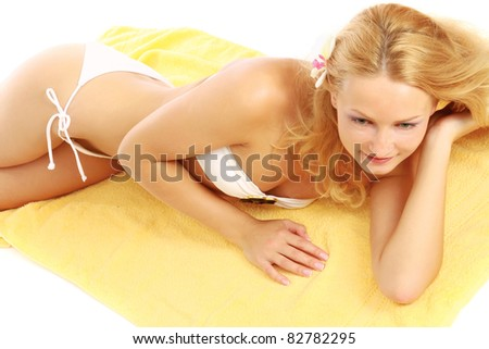 Closeup of a female body in a swimsuit with sunglasses lying on the beach, isolated on white