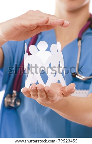 Closeup of a female doctor holding paper people, isolated on white - stock photo