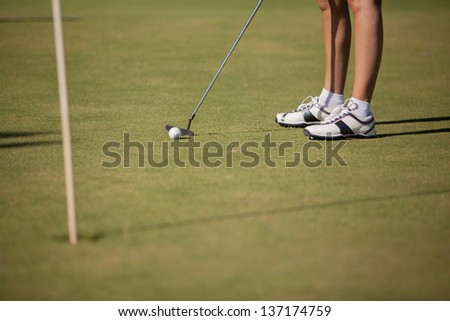Closeup of a female golfer playing in the green. Focus on Golfer.