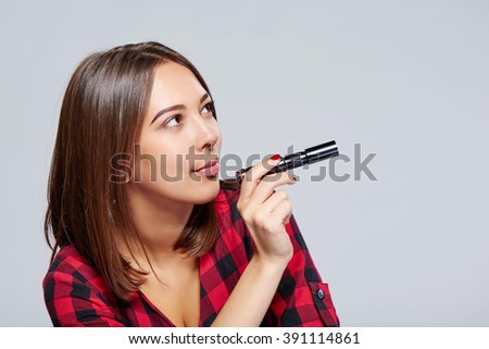 Closeup of a female holding pocket flashlight directing it at blank copy space, over grey background - stock photo
