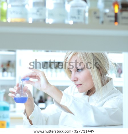 Closeup of a female researcher carrying out an experiment in a lab - stock photo