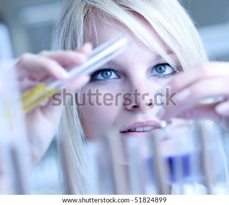 Closeup of a female researcher carrying out experiments in a lab - stock photo