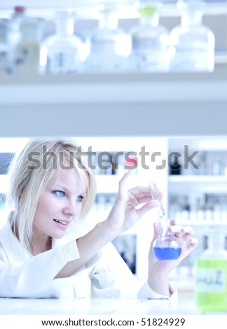 Closeup of a female researcher holding a test tube and a retort and carrying out experiments in a laboratory - stock photo