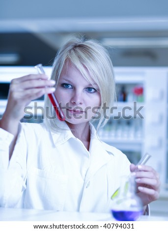 Closeup of a female researcher holding test tubes carrying out experiments in a lab - stock photo