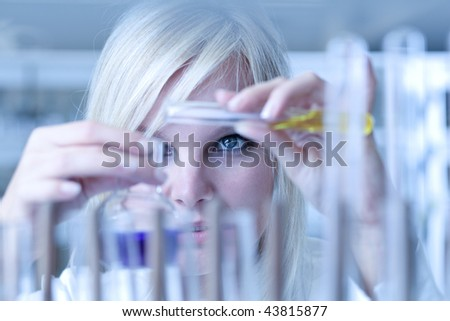 Closeup of a female researcher holding up a test tube and a retort and carrying out experiments (color toned image) - stock photo