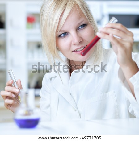 Closeup of a female researcher holding up a test tube and a retort and carrying out experiments - stock photo