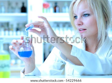 Closeup of a female researcher holding up a test tube and a retort and carrying out some experiments (color toned image) - stock photo
