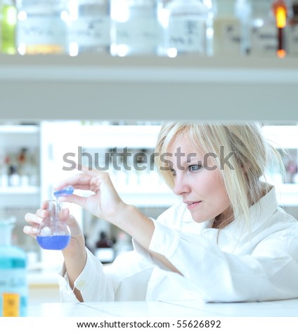 Closeup of a female researcher holding up a test tube and a retort and carrying out some experiments - stock photo