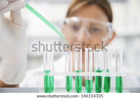 Closeup of a female scientist filling test tubes with pipette in laboratory