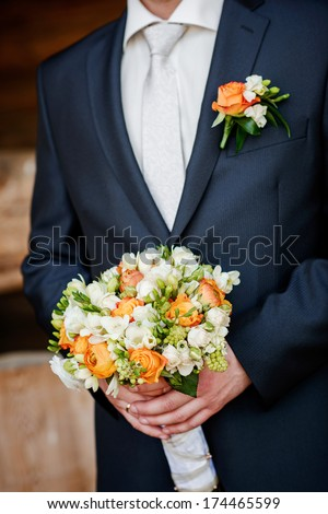 closeup of a fiance in suit with wedding flowers - stock photo