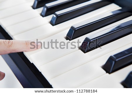 Closeup of a finger playing the piano. shot at studio