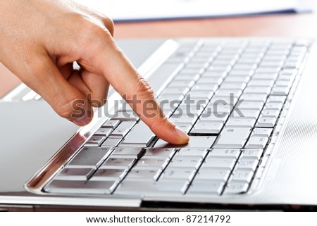 Closeup of a finger pressing the enter button - stock photo