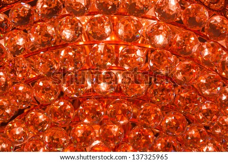 Closeup of a fire ruby crystal glass jewelry gem texture pattern background from a Chandelier