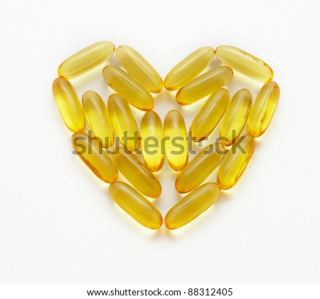 closeup of a fish oil supplements in a shape of a heart - stock photo