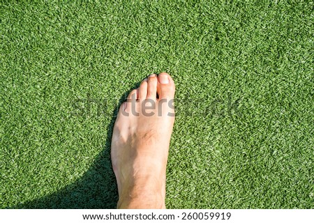 closeup of a foot of a man walking on the grass