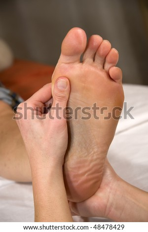 closeup of a foot of a natural mature woman having a foot reflex zone massage at the ball of the foot - stock photo
