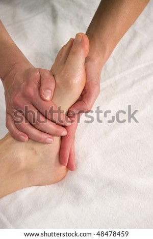 closeup of a foot of a natural mature woman having a massage at the sole of her foot - stock photo