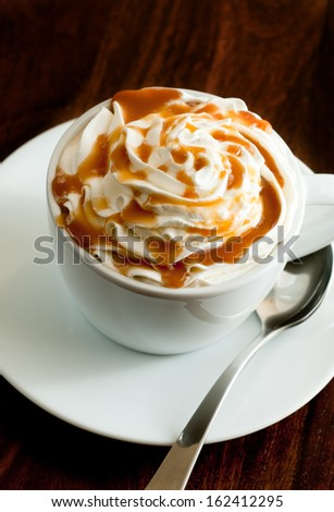 closeup of a fresh caramel latte with whipped cream - stock photo