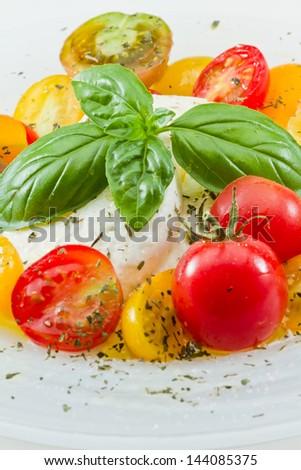 closeup of a fresh heirloom tomato and buffalo mozzarella salad garnished with fresh green basil - stock photo