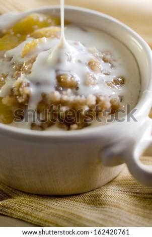 Closeup of a fresh peach cobbler with maple cream sauce. - stock photo