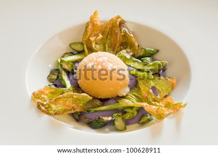 Closeup of a fried egg's yolk over purple potatoes cream with asparagus and dehydrated zucchini's flowers - stock photo
