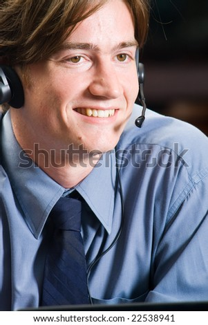 closeup of a friendly young male telephone operator - stock photo