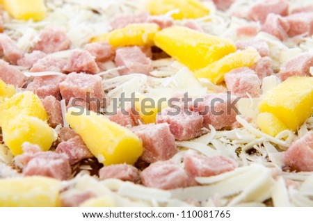 Closeup of a frozen hawaiian pizza with pineapple and ham. - stock photo